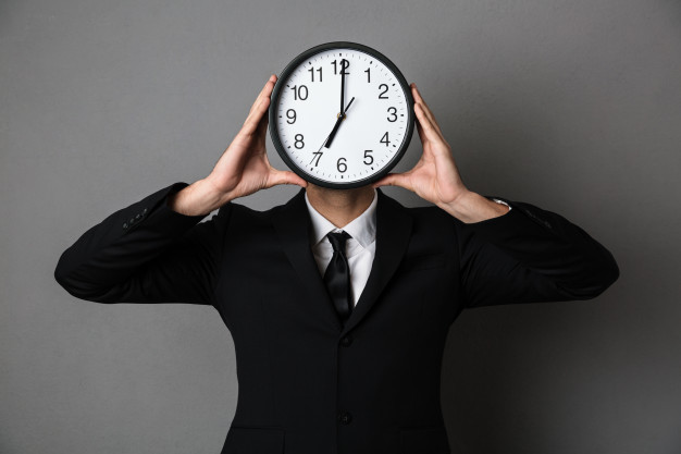 young-man-in-black-suit-holding-clock-in-front-of-his-face_171337-9695